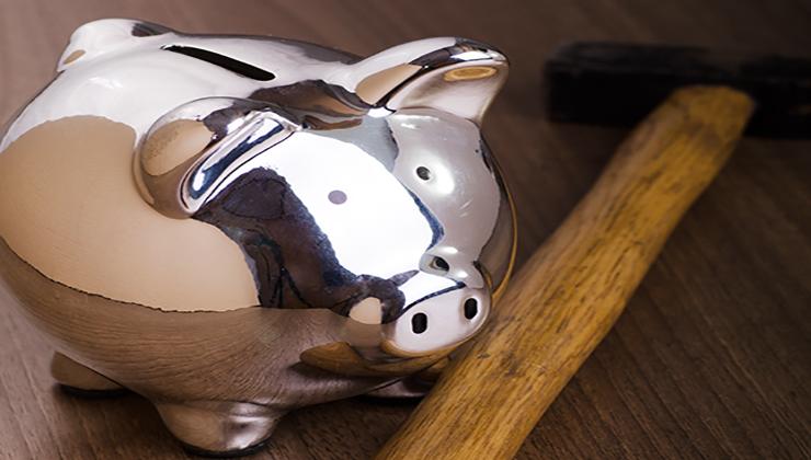 Zilveren spaarvarken en hamer